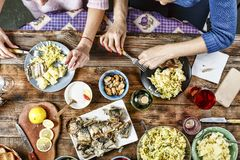 Dinner of friends. food, eating and family concept - group of people having breakfast and sitting at table. Top view royalty free stock photo