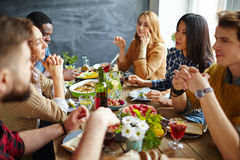 Dinner of friends. Group of intercultural friends having Thanksgiving dinner royalty free stock images