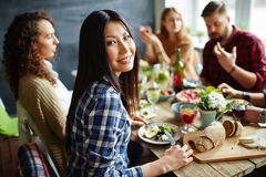 Dinner with friends. Pretty women sitting at table with friends and having dinner Royalty Free Stock Photo