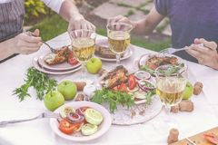 Dinner in the garden. People eat at the table with wine, grilled fish, fresh vegetables and herbs. Horizontal shot stock photo