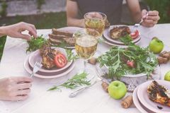 Dinner in the garden. People eat at the table with wine, grilled fish, fresh vegetables and herbs. Horizontal shot stock photos