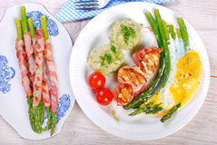 Dinner with green asparagus baked on eggs Royalty Free Stock Images