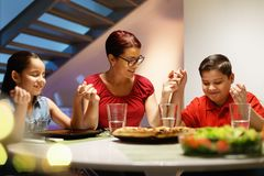 Dinner At Home With Happy Family Praying Before Eating. Hispanic family with mom, son and daughter praying before having dinner at home. Latino people with Royalty Free Stock Photos