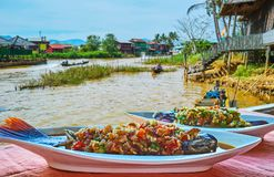 Dinner on Inle Lake, Myanmar. The restaurants on Inle Lake offer the tasty dishes of local fish with vegetables and herbs in Burmese style, Ywama, Myanmar royalty free stock photo