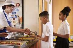 Dinner lady serving kids in a school cafeteria, side view stock images