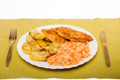 Dinner meal. Fried chicken roasted potatos and carrot salad. Royalty Free Stock Photo