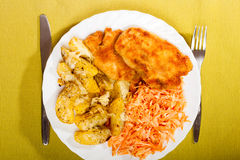 Dinner meal. Fried chicken roasted potatos and carrot salad. Stock Photo