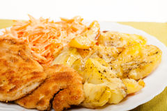 Dinner meal. Fried chicken roasted potatos and carrot salad. Royalty Free Stock Images