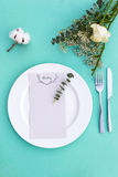 Dinner menu for a wedding or luxury evening meal. Table setting from above. Elegant empty plate, cutlery and flowers. Royalty Free Stock Photography