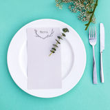 Dinner menu for a wedding or luxury evening meal. Table setting from above. Elegant empty plate, cutlery and flowers. Royalty Free Stock Photos