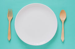 Dinner minimal background concept. Top view of empty white plate. With wooden fork and spoon on blue background. Flat lay Stock Images