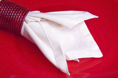 Dinner Napkin Bottom. White cloth napkin in a red basket weave napkin ring laying on a red dinner plate Stock Photography