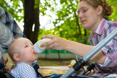 Dinner on the nature 2. Small child drinks milk sitting in a carriage Royalty Free Stock Images