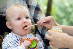 Dinner on the nature. Small child eats apple sauce from the spoon sitting in a carriage Stock Photos