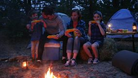 Dinner near flames on nature, family eat corn with salt, travel camping, mama, daddy and sons eat up fresh yellow maize. From out fire, at night in open air stock video footage