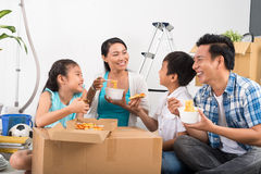 Dinner in new house. Vietnamese family sitting on the floor and eating noodles and pizza in their new house Stock Photo