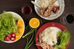 Dinner od turkey meat with rice, lettuce salad with radish, oran Stock Photos