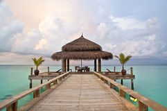 Dinner in paradise. Restaurant table over turquoise waters at dusk, ready for dinner Stock Photo