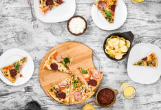 Dinner with pieces of pizza on board and plates Royalty Free Stock Photography