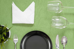 Dinner place setting a black plate with silver fork and spoon on. Green stock images