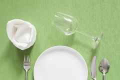 Dinner place setting a black plate with silver fork and spoon on Royalty Free Stock Photography