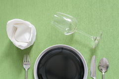dinner place setting a black plate with silver fork and spoon on Stock Images