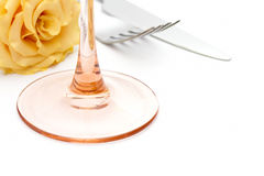 Dinner place setting. Knife and fork and glass with yellow rose Stock Image
