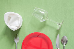 dinner place setting a red plate with silver fork and spoon on g Stock Images