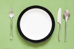 Dinner place setting a white plate with silver fork and spoon gr. Een royalty free stock photography