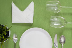 dinner place setting a white plate with silver fork and spoon on Stock Photos
