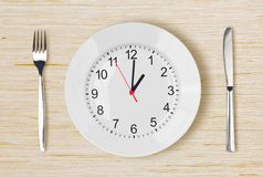 Dinner plate with clock face on wooden table. With fork an knife Royalty Free Stock Photo