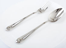 Dinner plate, spoon and fork. Royalty Free Stock Photos