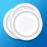 Dinner plates. On blue background Royalty Free Stock Photo