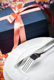 Dinner plates and cutlery with a gift Royalty Free Stock Photography