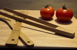 Dinner preparation. Two tomatoes and kitchen equipment placed on a cutting board Royalty Free Stock Image