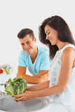 Dinner preparation. Couple washing vegetables. Focus on the woma stock photos