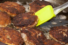 Dinner preparation, frying of meat chops. Process of frying of meat cutlets on a frying pan Royalty Free Stock Image