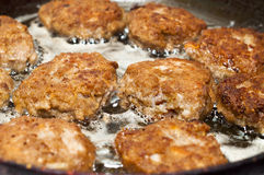 Dinner preparation, frying of meat. Process of frying of meat cutlets on a frying pan Royalty Free Stock Photography