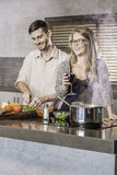 Dinner preparation  kitchen cooking happy young couple Royalty Free Stock Image
