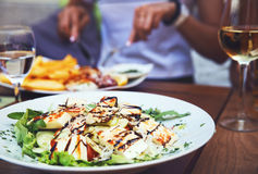 Dinner at restaurant. Close-up salad with grilled cheese.  People eating on the background Stock Photography