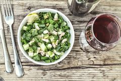 Dinner at the restaurant.Delicious seafood salad with avocado and wine in a glass. Delicious seafood salad with avocado and wine in a glass. Dinner at the Stock Photography