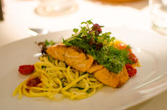 Dinner with roasted salmon. Roasted salmon with herb crust and pasta with lemon sauce. Garnished with watercress and sautéed cherry tomatoes Royalty Free Stock Image