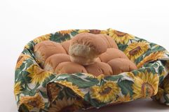 Dinner Rolls in a Basket 2. Dinner Rolls in a basket and material with a sunflower print, photographed on a white background stock photos