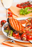 Dinner with salmon steak. And tomatoes Royalty Free Stock Images