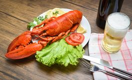 Dinner seafood lobster steamed on plate seafood with lemon salad lettuce vegetable and tomato / Beer glass on table. Dining with spoon fork wooden background royalty free stock photography