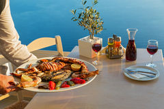 Dinner with seafood and red wine. On the background of sea sunset Stock Photos