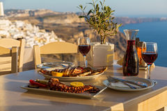 Dinner with seafood and red wine. On the background of sea sunset Stock Image