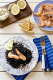 Dinner served with shrimps, black seaweed, breadsticks and lemon Royalty Free Stock Photography