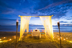 Dinner set up on the beach sunset time stock photo