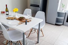 Dinner setting for two served in kitchen. Modern kitchen design. Roasted meat with wine in dining room. Dinner setting for two served in kitchen. Modern kitchen stock photos